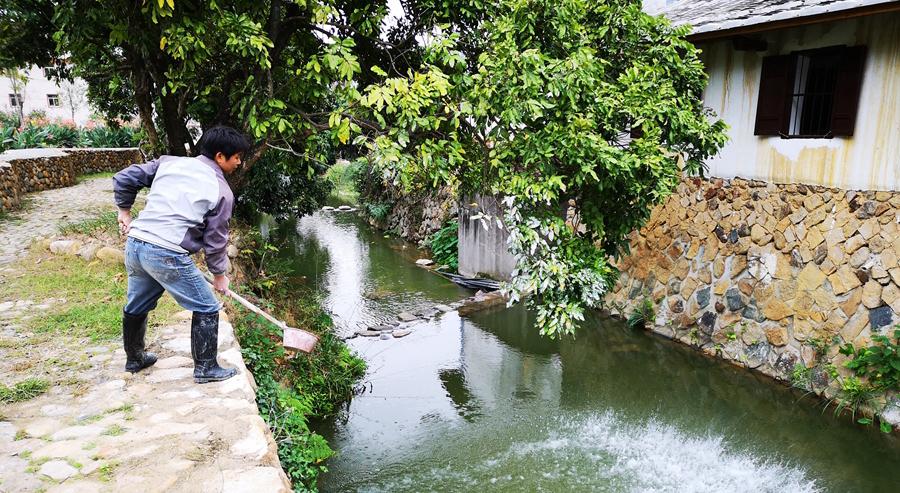 永春南星溪一名河道專管員用生石灰水潔凈溪水(資料圖)