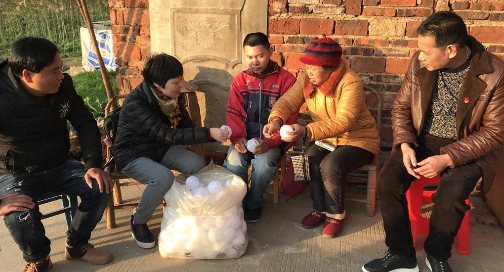 福建省稅務局派駐南平市延平區明前街村第一書記鬱華(左二)到貧困戶家中了解手工藝品的生産情況。